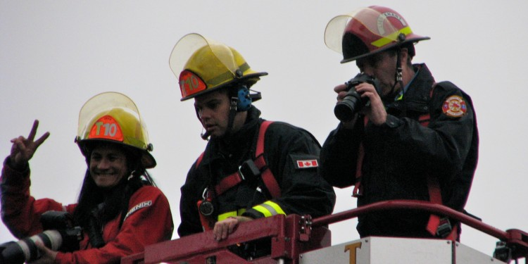 Firefighters taking pictures of the Olympic Flame Relay